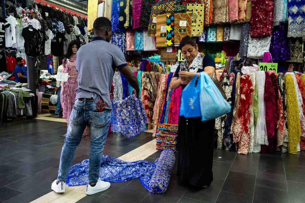 una donna indiana compra delle stoffe al Mercato Esquilino