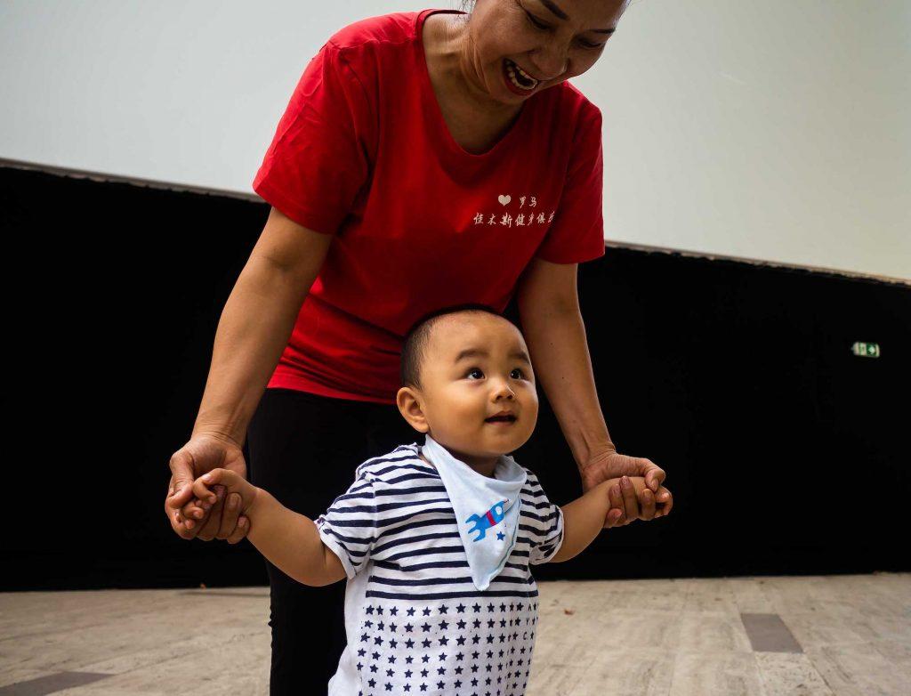 una signora cinese dopo aver finito la ginnastica mattutina a piazza Vittorio gioca con un bambino